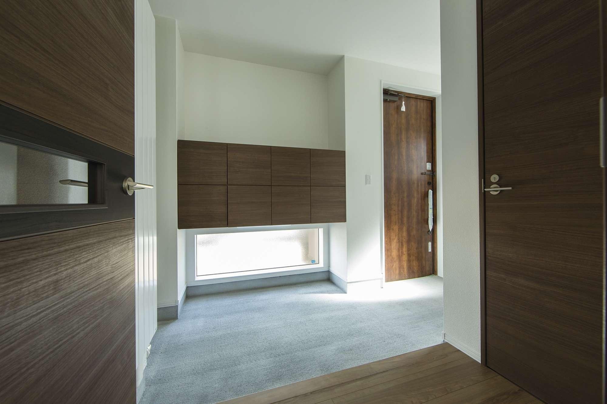 広い土間玄関。収納の下は地窓で光を取り入れる -  -  -